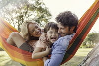 Family relaxing together on hammock, portrait