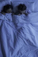 Couple lying together in bed scared
