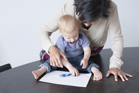 Grandmother and baby drawing together