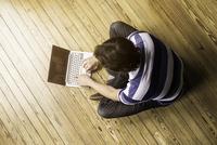 Man sitting indian style on floor using laptop computer