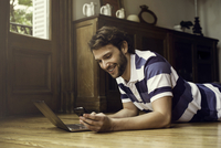 Man lying on floor using laptop and smartphone