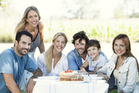 Family having picnic together outdoors, group portrait