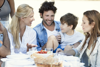 Family eating meal together outdoors 11001063937| 写真素材・ストックフォト・画像・イラスト素材|アマナイメージズ