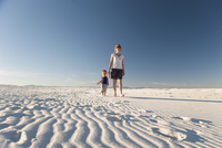 Mother and son walking on dune, White Sands National Monument, New Mexico, USA