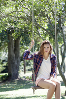 Young woman sitting on swing in park, portrait
