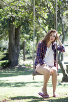 Young woman sitting on park swing with sad expression on face