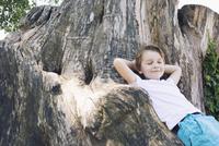Boy leaning against big tree trunk 11001063978| 写真素材・ストックフォト・画像・イラスト素材|アマナイメージズ