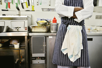 Chef standing in commercial kitchen with arms folded, mid section 11001063987| 写真素材・ストックフォト・画像・イラスト素材|アマナイメージズ
