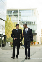 Businessmen having conversation while walking on sidewalk