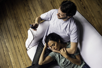 Man texting while girlfriend naps resting head on his lap
