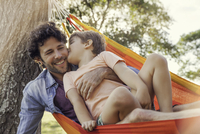 Father and son relaxing together in hammock 11001064026| 写真素材・ストックフォト・画像・イラスト素材|アマナイメージズ