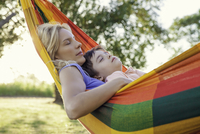 Mother and son napping together in hammock 11001064040| 写真素材・ストックフォト・画像・イラスト素材|アマナイメージズ