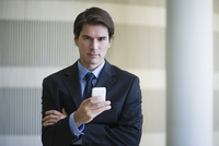 Businessman text messaging with cell phone, portrait 11001064080| 写真素材・ストックフォト・画像・イラスト素材|アマナイメージズ