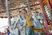 Little girl riding on carousel 11001064092| 写真素材・ストックフォト・画像・イラスト素材|アマナイメージズ