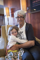 Grandmother and granddaughter embracing in chair, portrait