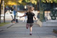 Little girl running on sidewalk