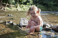 Little girl playing in shallow stream