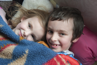Young siblings lying under blanket together, portrait