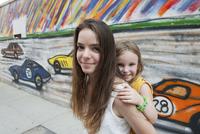 Teenage girl giving her little sister a piggyback ride, portrait