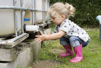 Little girl washing hands under outdoor cistern spigot