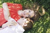Mother and boy lying on grass 11001064188| 写真素材・ストックフォト・画像・イラスト素材|アマナイメージズ