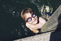 Boy with goggles swimming in water