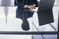 Businessman using laptop computer, reflection on glass top table