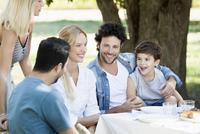 Friends enjoying meal and talking outdoors 11001064208| 写真素材・ストックフォト・画像・イラスト素材|アマナイメージズ
