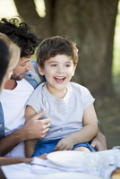 Little boy sitting on father's lap at outdoor meal 11001064212| 写真素材・ストックフォト・画像・イラスト素材|アマナイメージズ