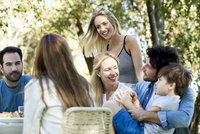 Friends and family enjoying meal together outdoors 11001064217| 写真素材・ストックフォト・画像・イラスト素材|アマナイメージズ