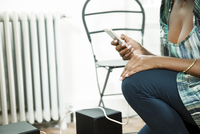 Woman playing music stored on smartphone over home stereo
