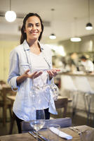 Waitress setting table at restaurant, portrait