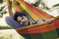 Man relaxing in hammock, portrait