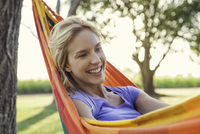 Woman relaxing in hammock, portrait