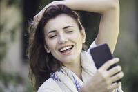Woman taking selfie 11001064331| 写真素材・ストックフォト・画像・イラスト素材|アマナイメージズ