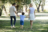 Family with one child taking walk outdoors together