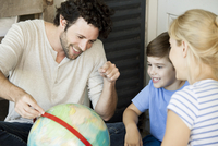 Family with one child looking at world globe together