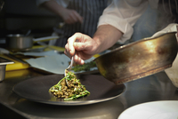 Chef spooning lentil dish onto serving plate 11001064371| 写真素材・ストックフォト・画像・イラスト素材|アマナイメージズ