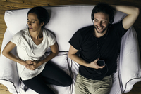 Woman holding stomach in pain while husband listens to mp3 player