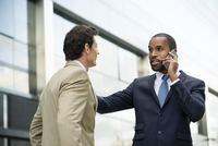 Businessman standing with colleague outdoors, talking on cell phone