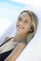 Woman relaxing beside pool, portrait