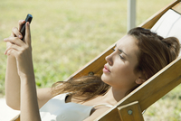 Young woman looking at smartphone while sunbathing