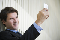 Man using smartphone to take a selfie