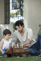 Father and son playing with toys in backyard