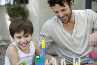 Father and son laughing while playing with toys