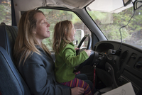 Little girl sitting on mother's lap behind steering wheel of car