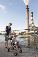 Mother pushing children in stroller near power plant 11001064465| 写真素材・ストックフォト・画像・イラスト素材|アマナイメージズ