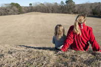 Mother and daughter sitting together on hill, rear view 11001064469| 写真素材・ストックフォト・画像・イラスト素材|アマナイメージズ