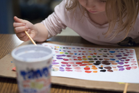 Little girl painting with watercolors