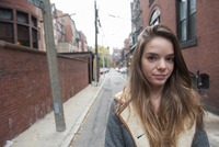 Teenage girl standing in alley, portrait
